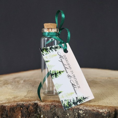Buteleczka na herbatę i personalizowanym bilecikiem z graficznym motywem lasu