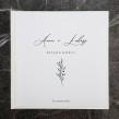 Biała minimalistyczna księga gości weselnych z prostym motywem gałązki