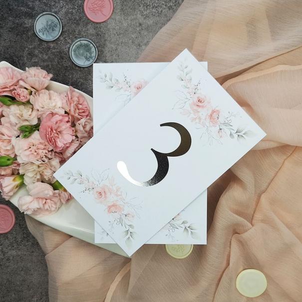 Eleganckie numerki na stół weselny ze srebrzeniem i pastelowymi różami