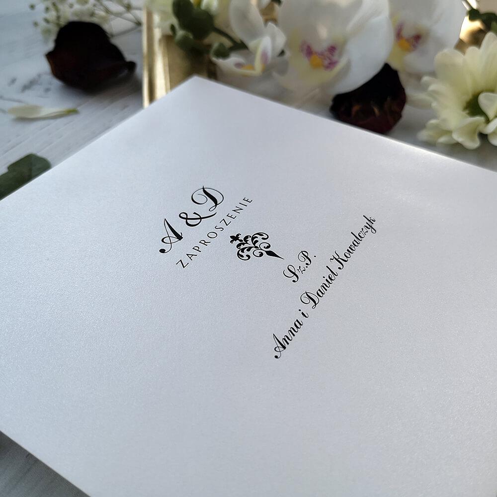 Biała koperta ozdobna z nadrukiem nazwisk gości weselnych.