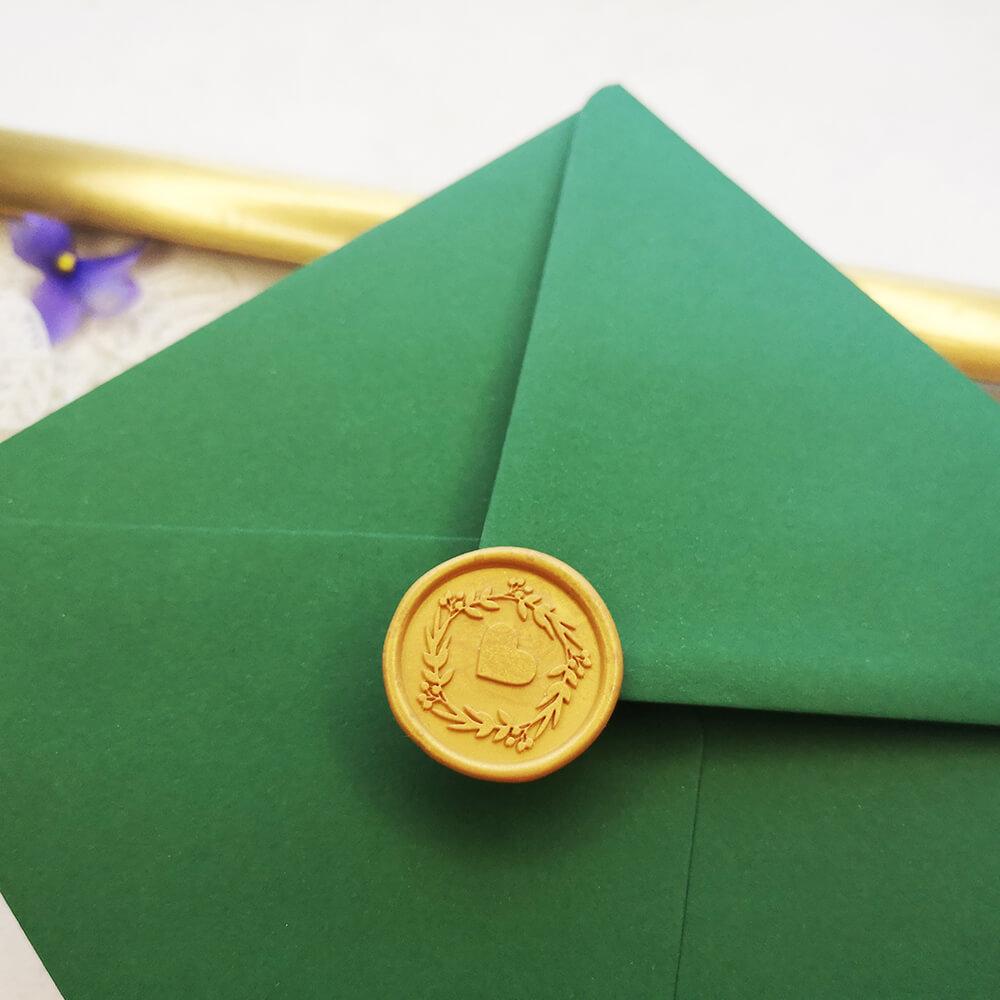 Złoty lak ślubny z sercem przyklejony do zielonej koperty